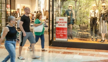 """People walking past a women's clothes store's """"mid-season sale"""" at the Azrieli Mall, Tel Aviv, September 2015."""