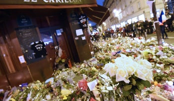 People gather in front of a makeshift memorial outside Le Carillon cafe, on November 16, 2015 at the in tribute to the victims of the Paris attacks.