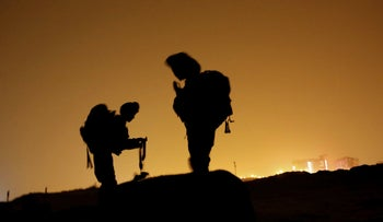 The silhouettes of two Israel Defense Forces soldiers during a nighttime exercise on the coast of Ashdod, November 2015.