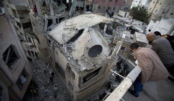 Palestinians look at a house that was demolished by the Israeli army, in the Qalandia refugee camp on the outskirts of the West Bank city of Ramallah, Monday, Nov. 16, 2015. Two Palestinians were killed and three wounded in clashes with Israeli troops early Monday in a Palestinian refugee camp in the Jerusalem area, a Palestinian health official said. The Israeli military said its troops entered Qalandia to demolish the home of a Palestinian who it says shot and killed an Israeli motorist in the West Bank this summer after he stopped to give the Palestinian directions to a nearby spring.