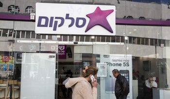 A woman walks past a branch of Cellcom, Israel's No. 1 mobile phone operator, in Tel Aviv, Israel, in this file picture taken January 28, 2014.