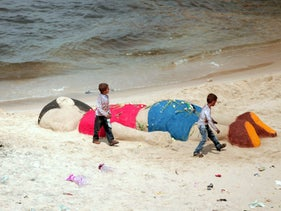 Two Palestinian boys play by a sand sculpture paying tribute to three year-old Syrian boy Alan Kurdi, Sept. 7, 2015.