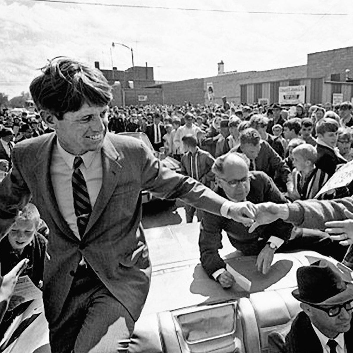 Robert F. Kennedy rides through Los Angeles in 1968 in his typical campaign pose: standing in an open-air car, smiling and reaching out to touch the endless hands that greet him.