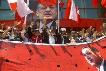 Erdogan supporters wave their hands, in making a four-fingered gesture referring to the Muslim Brotherhood, in Sidon, Lebanon, July 16, 2016.