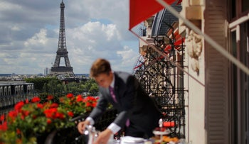 An employee prepares breakfast in front of the Eiffel tower at a luxury hotel in Paris, France. July 30, 2015.