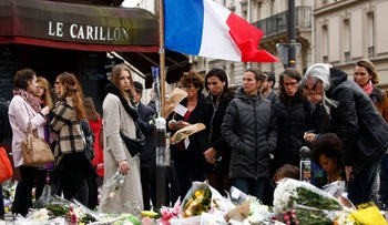 "People mourn outside ""Le Petit Cambodge"" and ""Le Carillon"" restaurants in the wake of Friday's deadly terror attacks. November 17, 2015."