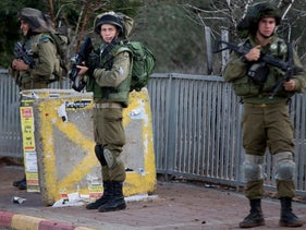 Israeli soldiers stand guard at a bus stop in the West Bank, near the Palestinian town of Nablus, November 8, 2015.