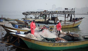 Palestinian fishermen fix the net on their boat in the seaport of Gaza City, January 26, 2015.