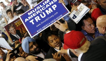 U.S. Republican presidential candidate Donald Trump signs autographs for supporters holding a Muslim Americans for Trump sign after a rally in Harrington, Delaware April 22, 2016.