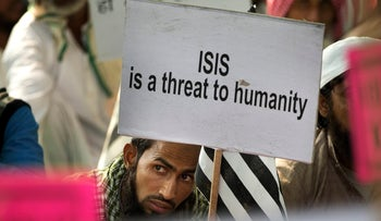An Indian Muslim man holds a banner during a protest against ISIS and the Paris attacks, in New Delhi, India, November 18, 2015.