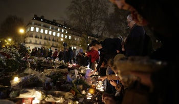 People light candles at a makeshift memorial for the victims the deadly attacks in Paris at the Place de la Republique, November 20, 2015.