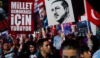 People hold placards with a picture of Turkish President Recep Tayyip Erdogan during a rally at Kizilay Square, Ankara, Turkey, July 20, 2016.