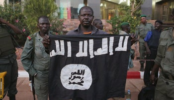 Malian security officials show a jihadist flag they said belonged to attackers in front of the Radisson hotel in Bamako, Mali, November 20, 2015.