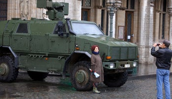 Tourists taking pictures in front of a military armored vehicle in central Brussels, November 21, 2015.