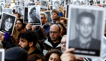 People hold up pictures of the victims of the AMIA Jewish center bombing during a ceremony to mark the 22nd anniversary of the 1994 attack, Buenos Aires, Argentina, July 18, 2016.