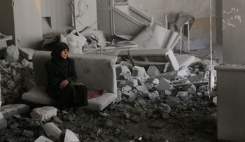 A Syrian woman shelters in a damaged building as civil defense workers sift through debris looking for survivors following reported airstrikes, eastern Aleppo, Syria, July 14, 2016.