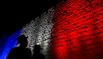 Two Ultra-Orthodox Jews look at Jerusalem's Old City walls illuminated by the colors of the French national flag, November 15, 2015.