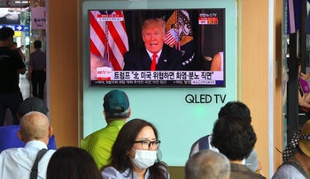 People watch a television news program showing U.S. President Donald Trump at a railway station in Seoul on August 9, 2017.