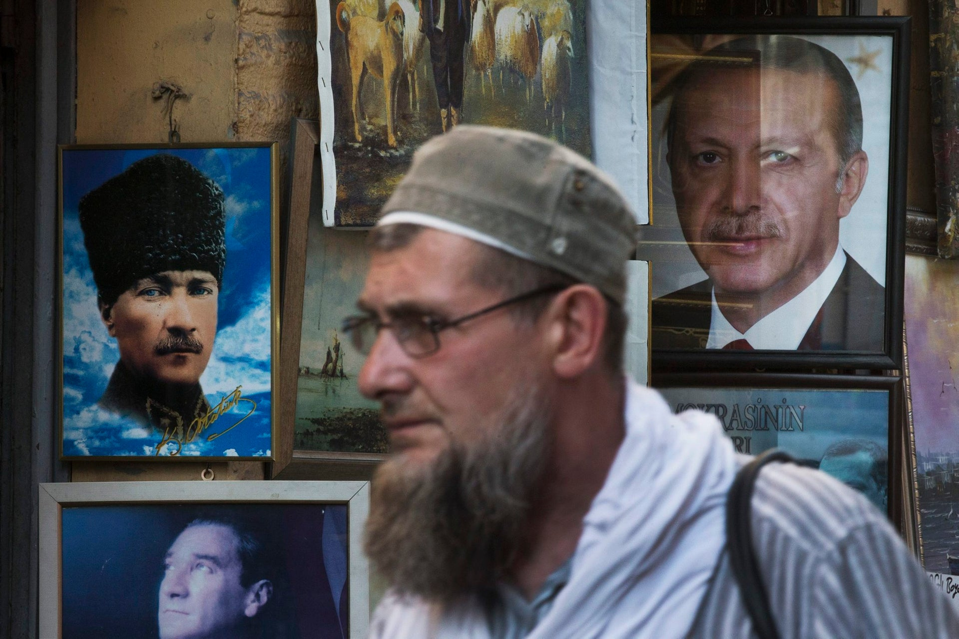 The portraits of Turkey's founder Kemal Ataturk, left, and current President Recep Tayyip Erdogan, right, are offered for sale in a shop as a man walks by, in Istanbul, July 21, 2016.