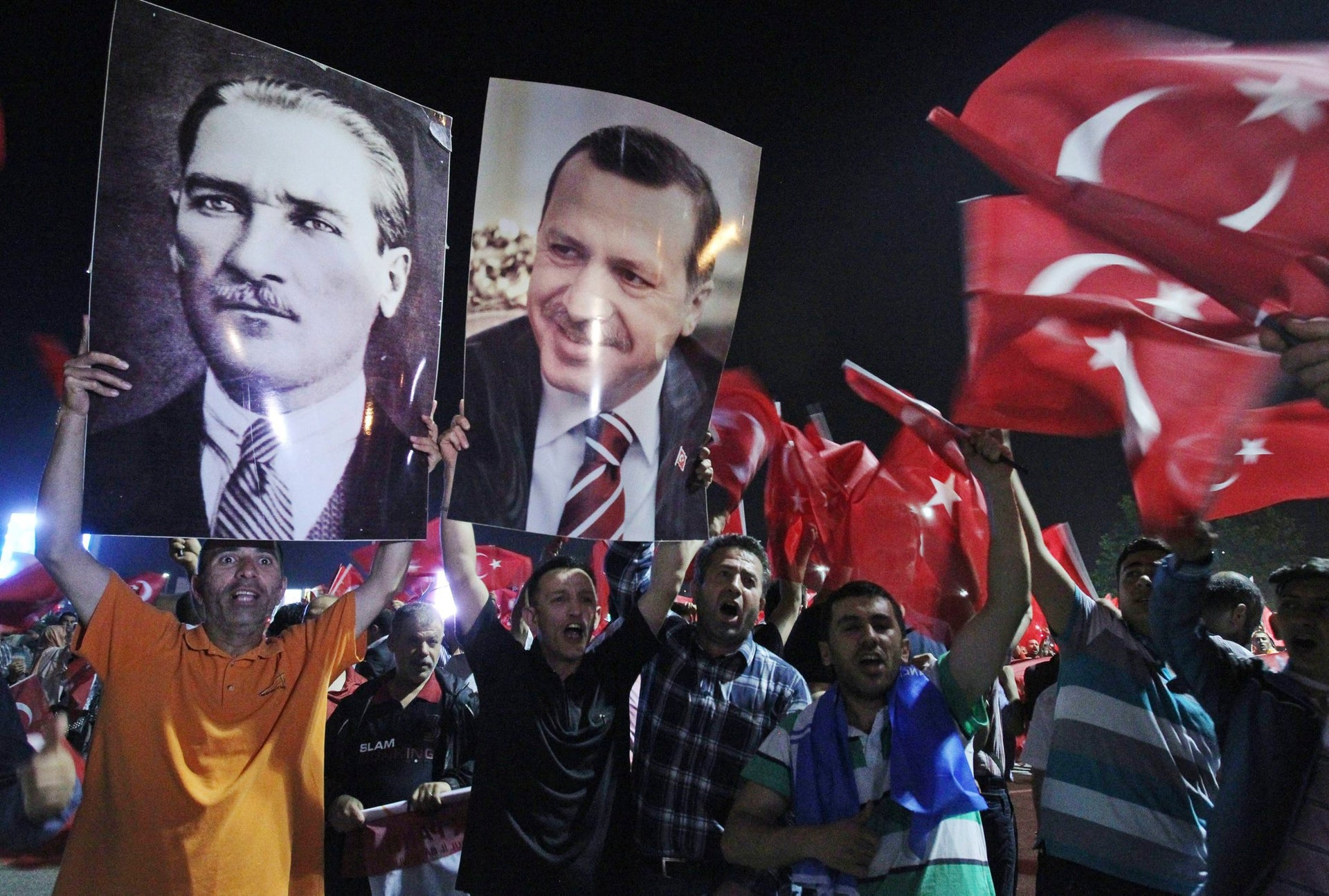 Supporters of the Justice and Development party hold the portraits of Mustafa Kemal Ataturk, left, and then-Prime Minister Recep Tayyip Erdogan, in June 2013.