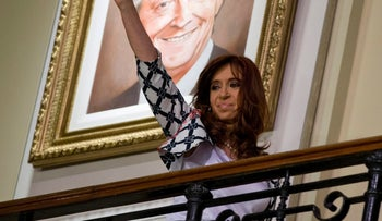 Argentina's President Cristina Fernandez waves at the government house in front of a painting of her late husband Nestor Kirchner in Buenos Aires, Argentina, Thursday, Oct. 29, 2015.