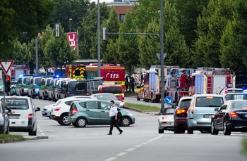 Police and firefighters wait at the scene of a shooting in a Munich shopping mall, July 22, 2016.