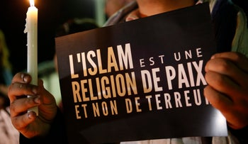 """Muslim man holds a banner witch read """"Islam is a religion of peace and not terror"""" as people gather in solidarity with French people one week after terror attacks."""