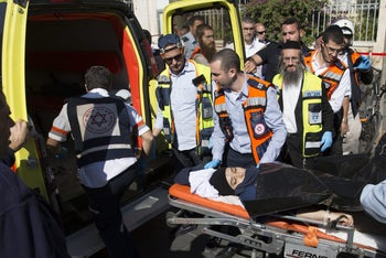 Israeli medics move a handcuffed Palestinian woman, who police believe attacked a man, at the scene of a stabbing attack in Jerusalem, Monday, Nov. 23, 2015.