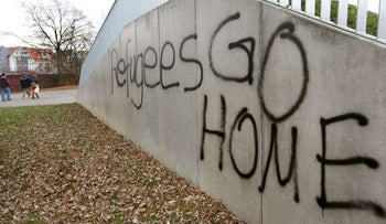 "The lettering ""Refugees GO HOME"" is sprayed onto a wall in Sigmaringen, southern Germany, on November 17, 2015, as some people in the background walk past the wall, which is on the side of an embankment."