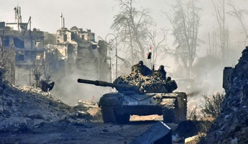 Syrian pro-government forces maneuver a tank in the newly retaken areas of Sahat al-Melh and Qasr al-Adly in Aleppo's Old City, Syria, December 8, 2016.