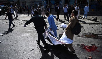 Afghan volunteers at the scene of a suicide attack that targeted crowds of minority Shi'ite Hazaras during a demonstration in Kabul, July 23, 2016.
