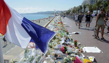 People walking a makeshift memorial to the victims of the Bastille Day truck attack near the Promenade des Anglais in Nice, July 21, 2016.