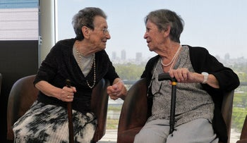 Sarah Aggasi (R), 90, who was an Irgun activist, shakes hands with Shona Levy Kampos, 91, who was injured in the 1946 King David Hotel blast.