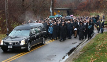 People walk behind the hearse, which is followed on foot to Sharon Memorial Park for the burial of Ezra Schwartz in Sharon, Mass., Sunday, Nov. 22, 2015.
