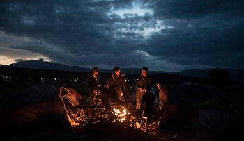 "Refugees warming themselves by a fire near the northern Greek village of Idomeni at the Greek-Macedonian border, on Monday, Nov. 23, 2015. Europe is already cooling to the flood of migrants: several countries say they will only allow ""war-zone refugees"" from Afghanistan, Iraq and Syria to transit through their countries on their way to central and northern Europe."
