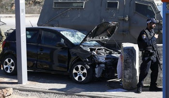 An Israeli policeman stands in front of a damaged car of a Palestinian, who Israeli army said drove into three Israeli soldiers at Tapuah Junction on Nov. 24, 2015.