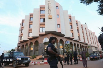 A Malian police officer stands guard in front of the Radisson hotel in Bamako, Mali, Nov. 20, 2014.