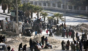 Syrian civilians arrive at a checkpoint manned by pro-government forces, at the al-Hawoz street roundabout, after leaving Aleppo's eastern neighborhoods on December 10, 2016.