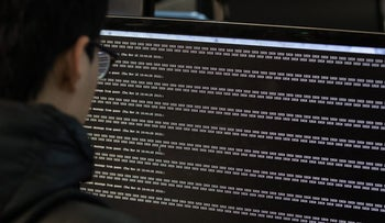 """A student looks at text reading """"ISIS"""" displayed on a computer monitor during a cyber-defense programming class in the """"War Room"""" at Korea University in Seoul, South Korea, on Thursday, Nov. 26, 2015. In a darkened """"war room"""" dozens of South Korea's brightest college students are practicing hacking each other as part of a government program to train them to battle some of the world's best -- the shadowy techno-soldiers of Kim Jong Un's regime. Photographer: SeongJoon Cho/Bloomberg"""
