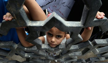 A Palestinian girl looks through the gate of Rafah border crossing between Egypt and Gaza during a protest calling on Egyptian authorities to open the crossing, in the southern Gaza Strip July 6, 2017. REUTERS/Ibraheem Abu Mustafa     TPX IMAGES OF THE DAY