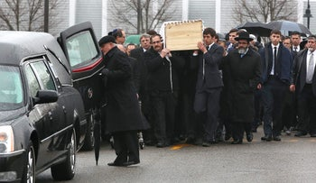 Mourners carry the casket of Ezra Schwartz to the hearse for burial in Sharon, Massachusetts. November 22, 2015.