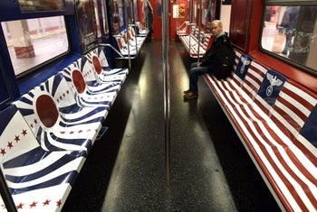 A passenger sits on a New York City Subway 42nd Street shuttle train covered in symbols from Nazi Germany and Imperial Japan on November 24, 2015.