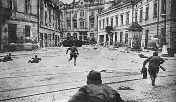 Soviet soldiers taking back Lwow (also known as Lviv) from German forces in July 1944. On the left of the picture we see two helmeted soldiers lying down, with one aiming rifles at forces we cannot see. In the foreground, center and right of the picture we see soldiers running, rifles in hand, towards forces we cannot see. There is a tank in the background but it is hard to see which way it is aimed.