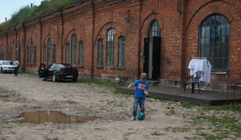 A boy playing soccer at the entrance to the former concentration camp known as the Seventh Fort in Kaunas, Lithuania, July 12, 2016.