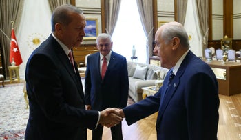 Erdogan shakes hands with Turkey's Chairman of the Nationalist Movement Party Devlet Bahceli as Yildirim looks on during a meeting with leaders of the main political parties in Ankara July 25, 2016.