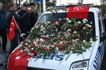 People leaving carnations and roses on a police car outside the Besiktas soccer club stadium in Istanbul, December 11, 2016.