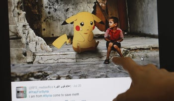 A journalist looks at a montage by a Syrian activist, using the international frenzy over the Pokemon Go game to draw new attention to the battle-scarred country, in Beirut on July 22, 2016.