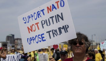 A protester carries a sign reading 'Support NATO- Not Putin- Oppose Trump' during a demonstration at the Republican National Convention on July 21, 2016.