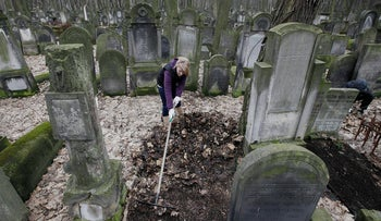 A volunteer helps to clean a Jewish cemetery in Warsaw, Poland, on Sunday April 14, 2013.