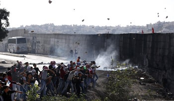 Palestinian demonstrators hurl rocks at Israeli forces next to the separation wall between West Bank's Abu Dis and East Jerusalem, November 2, 2015.